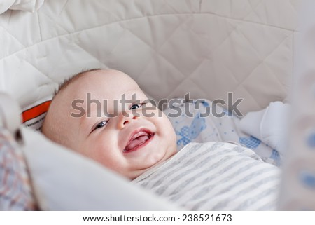 Cute  baby smiling looking at the camera lying in the cradle