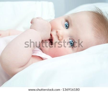 cute baby sucks his thumb lying in bed - stock photo
