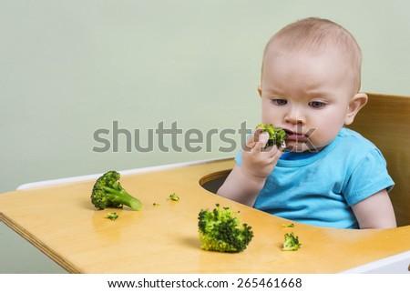 cute baby tasting broccoli - stock photo