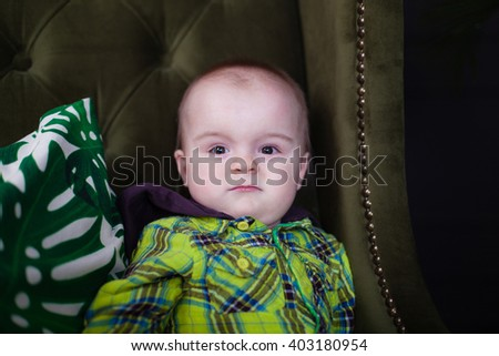 Cute baby toddler sitting on a green armchair near white checkered pillow, fool around, closeup - stock photo