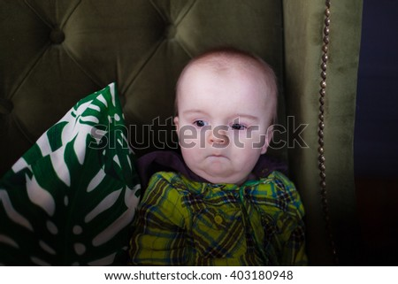 Cute baby toddler sitting on a green armchair near white checkered pillow, fool around, grimace - stock photo