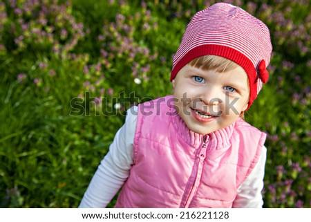 Cute baby walking on blooming meadow - stock photo