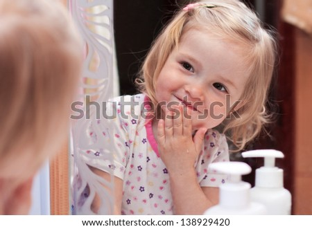 Cute baby washes his face and looks at himself in the mirror - stock photo