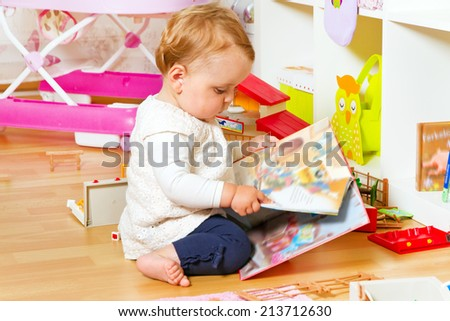 Cute baby with a colorful book - stock photo