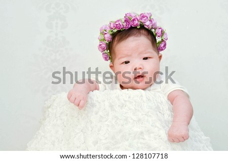 cute baby with a wreath of flowers on her head - stock photo