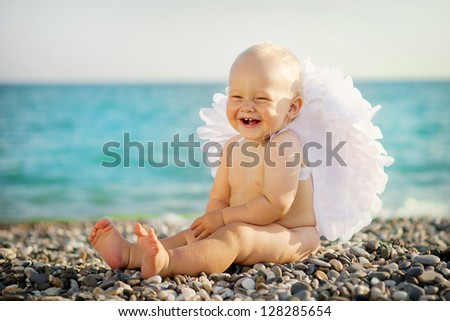 Cute baby with angel wings is sitting on the seashore - stock photo