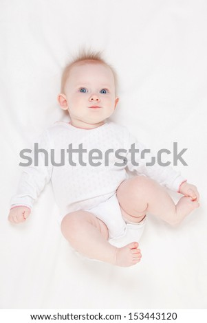 Cute baby with beautiful blue eyes lying in white bed - stock photo