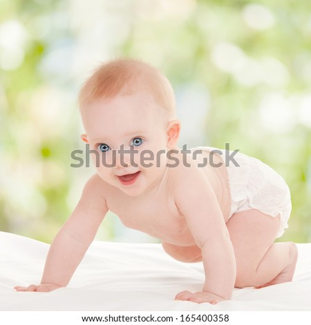 Cute baby with beautiful blue eyes on the white bed - stock photo