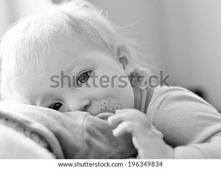 Cute baby with blue eyes hugging a mascot. MANY OTHER PHOTOS FROM THIS SERIES IN MY PORTFOLIO. - stock photo