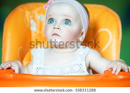 cute baby with blue eyes in orange chair - stock photo