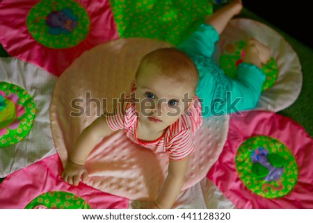 Cute baby with blue eyes looking up from colorful rug - stock photo