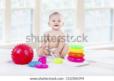 Cute baby with colorful toys at home - stock photo