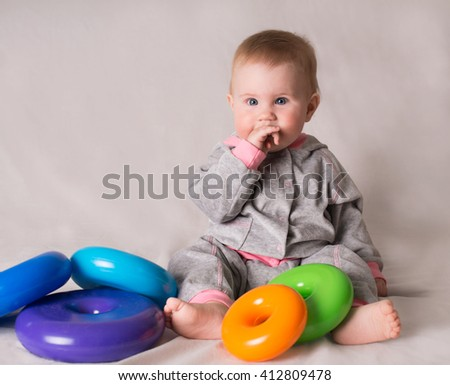 Cute baby with colorful toys on grey background.