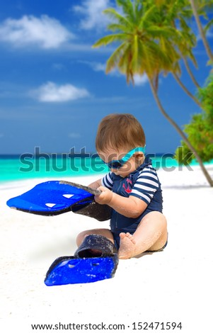Cute baby with diving costume or swimwear, sunglasses and flippers sitting on the tropical beach on Maldives - stock photo