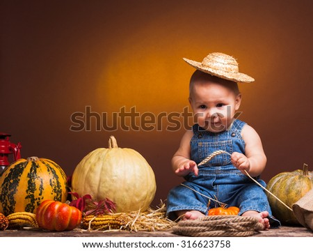 Cute baby with ears of wheat in the hands posing on the background of pumpkins. - stock photo