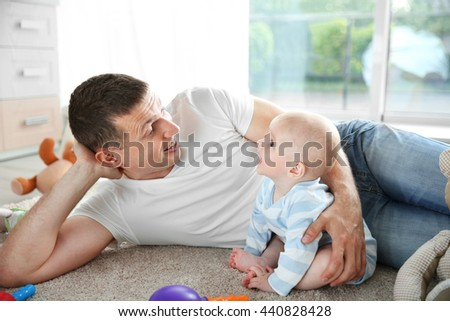 Cute baby with father on the floor - stock photo