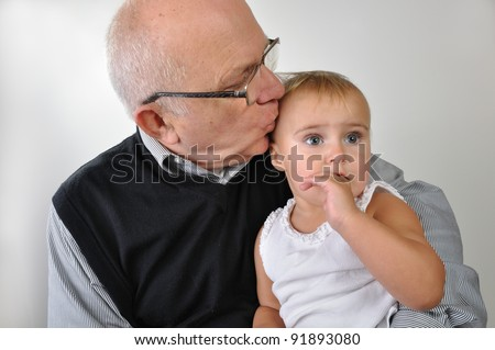Cute baby with finger in her mouse sitting on grandfatherâ??s lap - stock photo