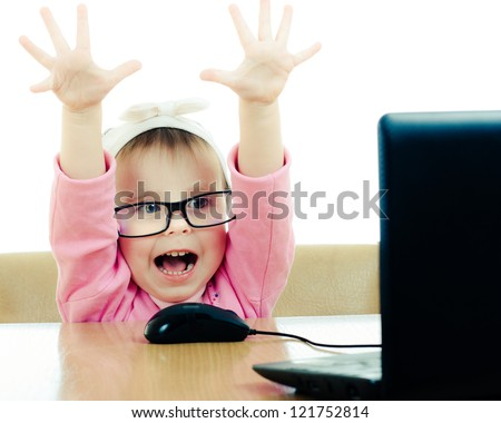 Cute baby with glasses looking into the laptop on a white background. - stock photo