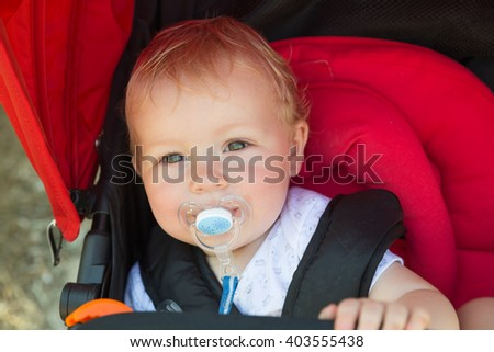 Cute baby with pacifier sitting in the stroller - stock photo