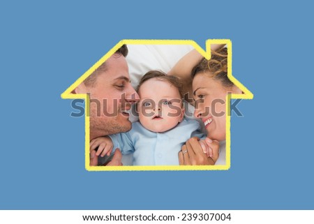 Cute baby with parents in bed against blue background with vignette - stock photo