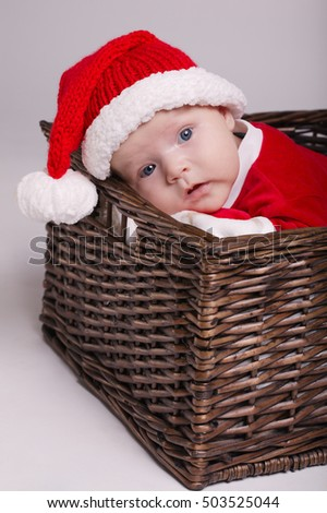 cute baby with santa costume lying in basket