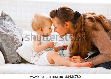 Cute baby with soother and young mom playing on divan at home - stock photo