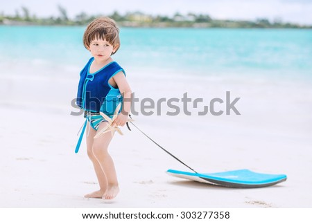 Cute baby with swimwear and life vest walking on the tropical beach with boogie board - stock photo