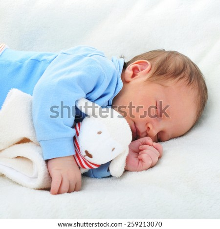 cute baby with toy sleeping on white blanket