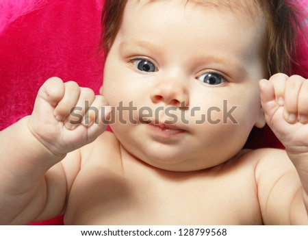 cute baby with wide opened blue eyes, beautiful kid's face and hands closeup, studio shot - stock photo