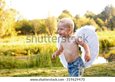 Cute baby with wings laughs and walks along the river bank - stock photo