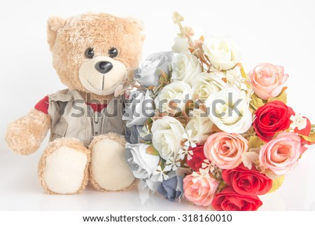 Cute bear doll with rose bouquet on vintage style on white - stock photo