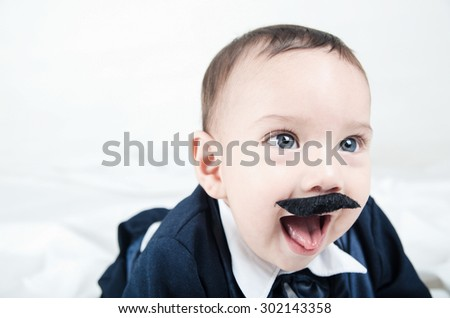 Cute beautiful baby boy in costume with mustache and suit white background close up