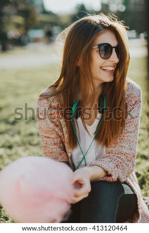 cute, beautiful caucasian white young lady enjoy warm spring sunset and eats cotton candy in a green park  while listens to the music with fashion style headphones - stock photo
