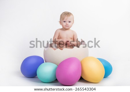 cute beautiful emotional baby sitting in easter egg with colored eggs around on white background - stock photo
