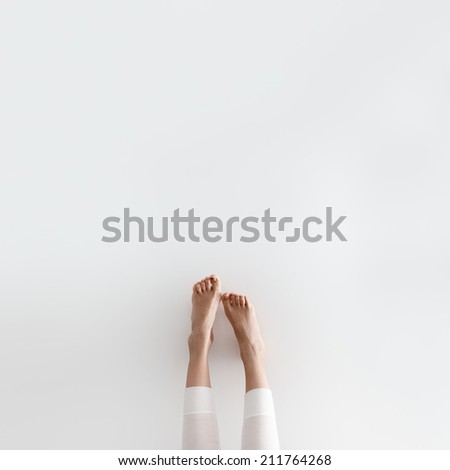 Cute beautiful gentle girl's legs in the morning on the wall - stock photo