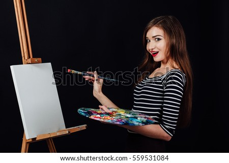 Cute beautiful girl artist painting a picture on a canvas on an easel. Space for text. Studio black background. Long hair, brunette. Holding colorful brush and palette. Red lipstick