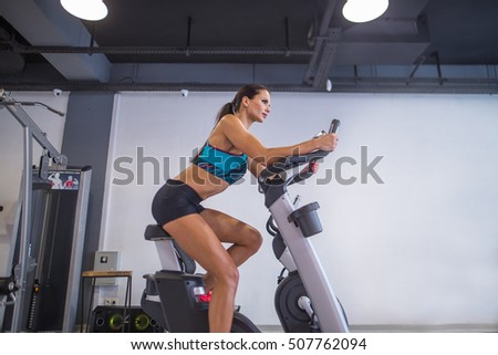 Cute beautiful girl pedaling on a stationary bike at the gym. In the background a gym. Girl dressed in a blue top and black shorts. Training on the simulator