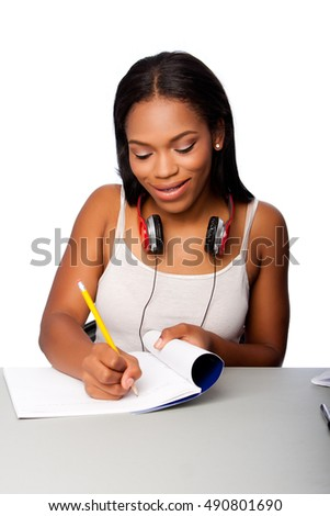 Cute beautiful happy smiling teenage student doing homework writing in notebook sitting at desk, on white.