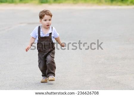 Cute beautiful little boy in brown suit, walks on asphalt road - stock photo