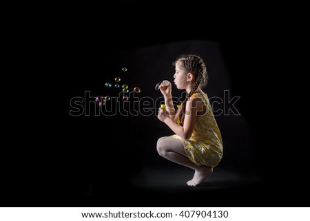 cute beautiful little girl and soap bubbles . happy child. girl blows soap bubbles on a black background - stock photo