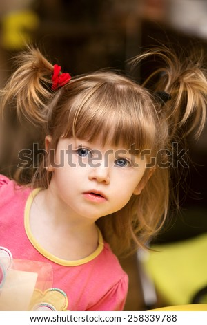 Cute beautiful little girl kid with two tails looks. Baby girl - stock photo