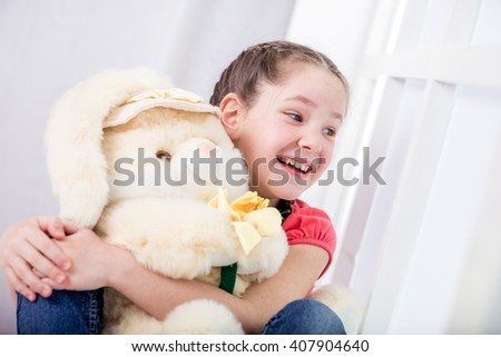 cute beautiful little girl smiles and hugs the toy rabbit. happy child with toy