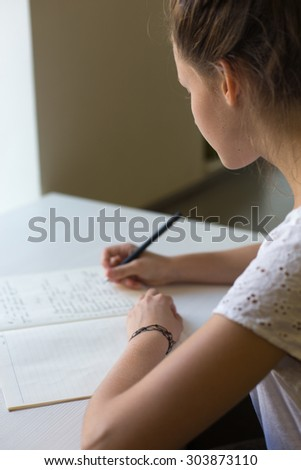 cute beautiful lonely teenager girl studying in the class writing down in her copybook - stock photo