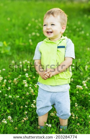 Cute beautiful smiling boy on summer meadow - stock photo