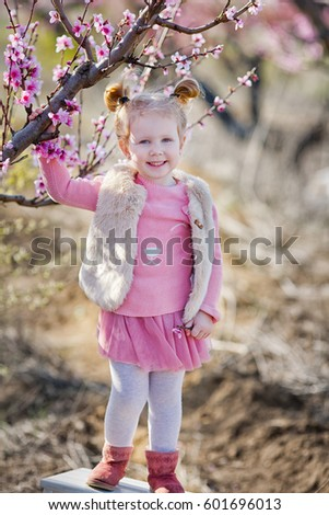 Cute beautiful stylish dressed blond girl standing on a field of spring young peach tree with pink flowers.smiling girl dressed in in pink in spring season.
