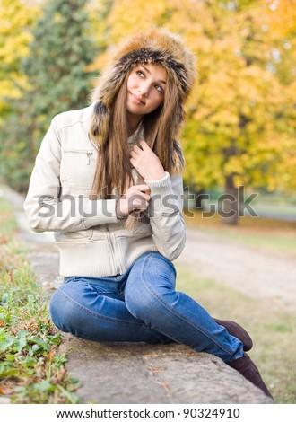 Cute beautiful young brunette girl posing outdoors in big russian style fur hat. - stock photo