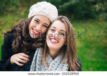 Cute best friend girls a piggyback in winter outdoors - stock photo