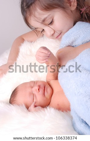 cute big sister looking over brand new newborn baby brother - stock photo