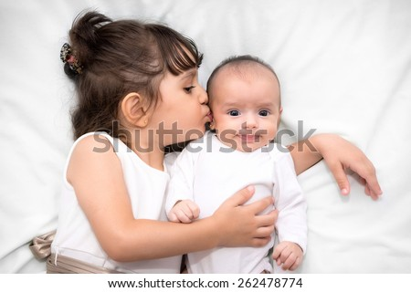 cute big sister with new newborn baby  - stock photo