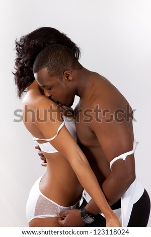 cute black couple kissing, man and woman in romantic play with passion and love; he is touching her while  she is tearing his shirt off - stock photo